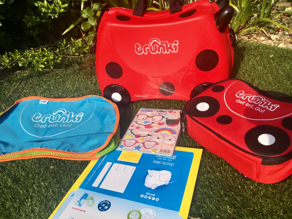 Travel with Trunki. The red and black spotted Trunki is on grass with the stickers, lunch bag and blue tidy bag next to it