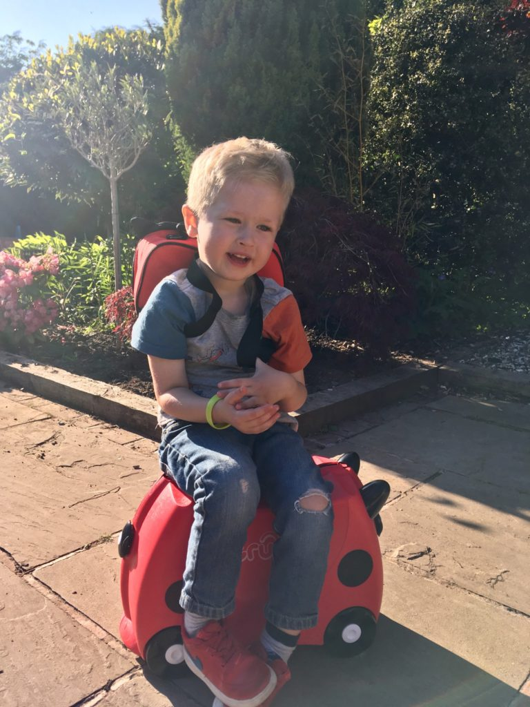 Travel with Trunki Lucas is sat on the Trunki looking at camera