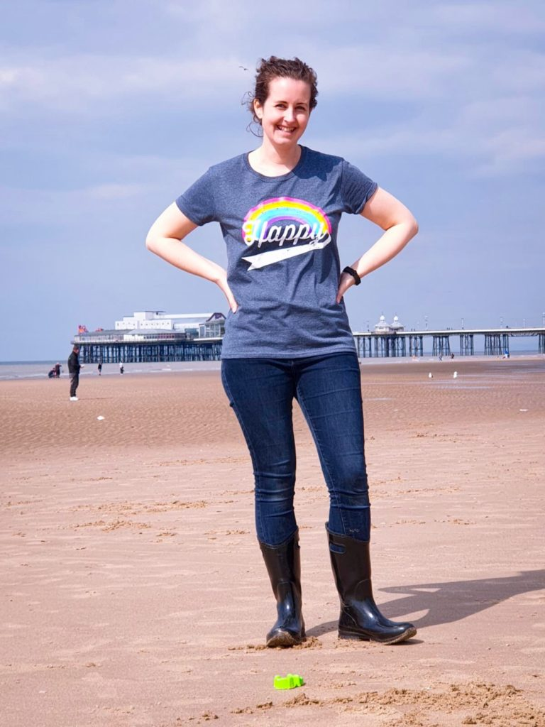 I'm standing in the beach with a pier behind me. I'm wearing the rainbow Happy T-shirt, jeans and black wellies