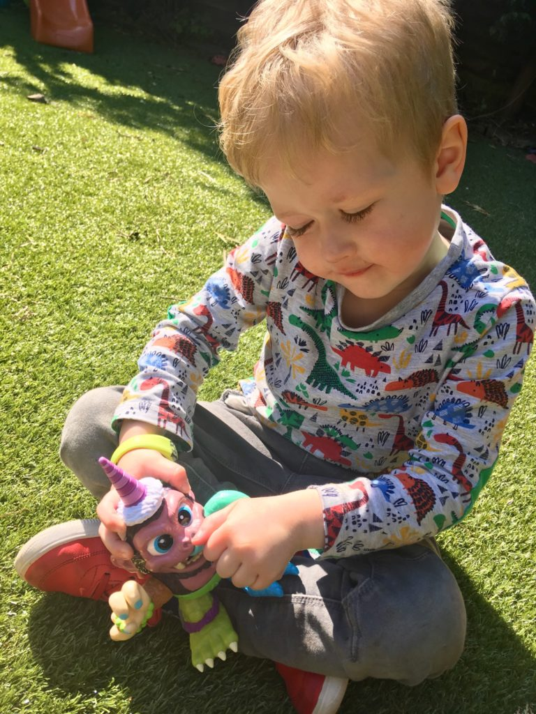 Crate Creatures. Lucas, a blonde 4 year old boy is sat on grass holding the crate creature in his hands, he is looking down at it