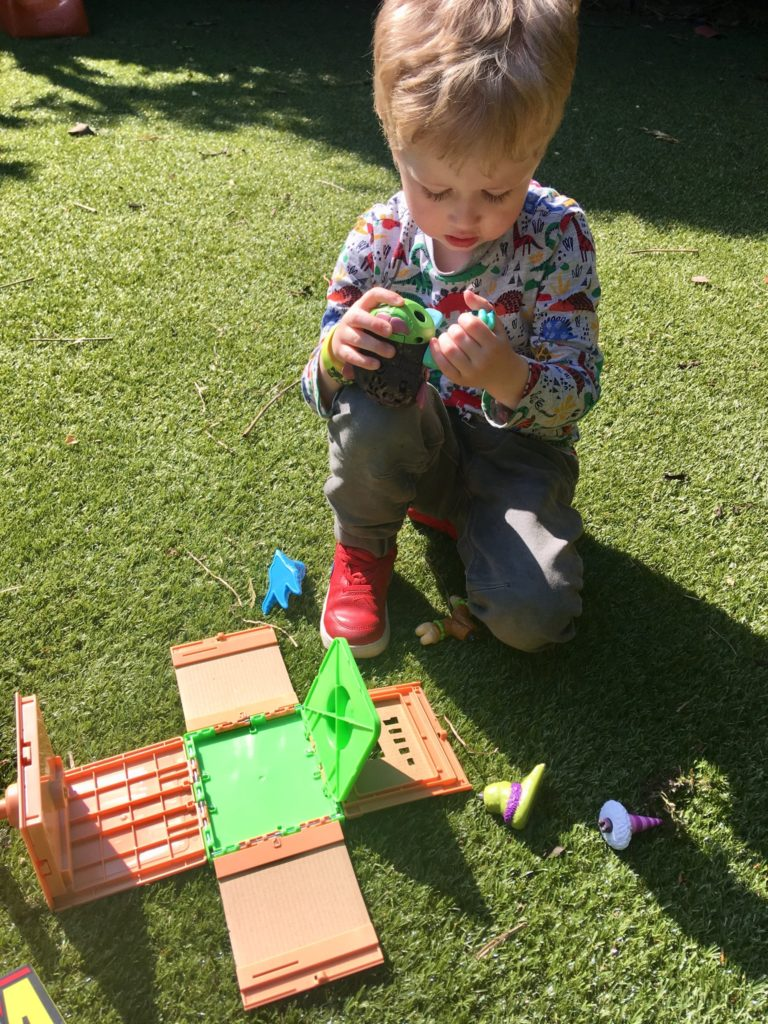 Crate Creatures. Lucas, a four year old blonde hair d boy is sat on the grass holding the monster crate creature in his hand. I'm front of him is the open crate