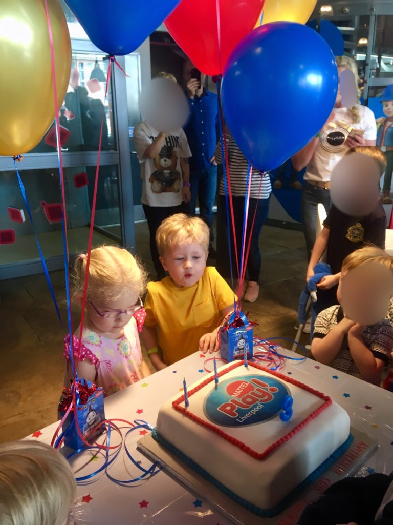 Lucas and Katie stood in front of the birthday cake