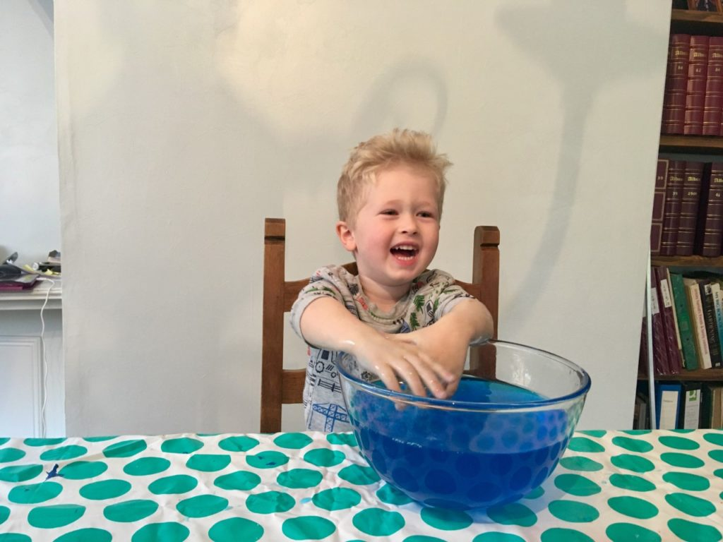 Lucas is sat at table with his hands in a big bowl of blue slime