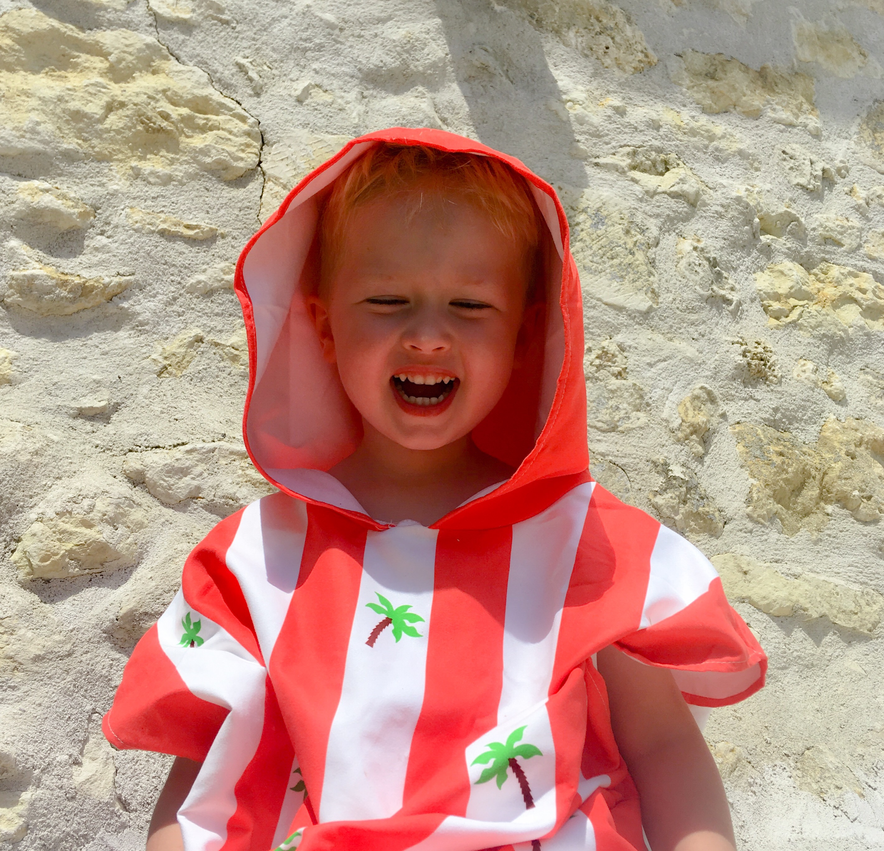Lucas sat smiling wearing a stripy orange and white poncho with palm trees on