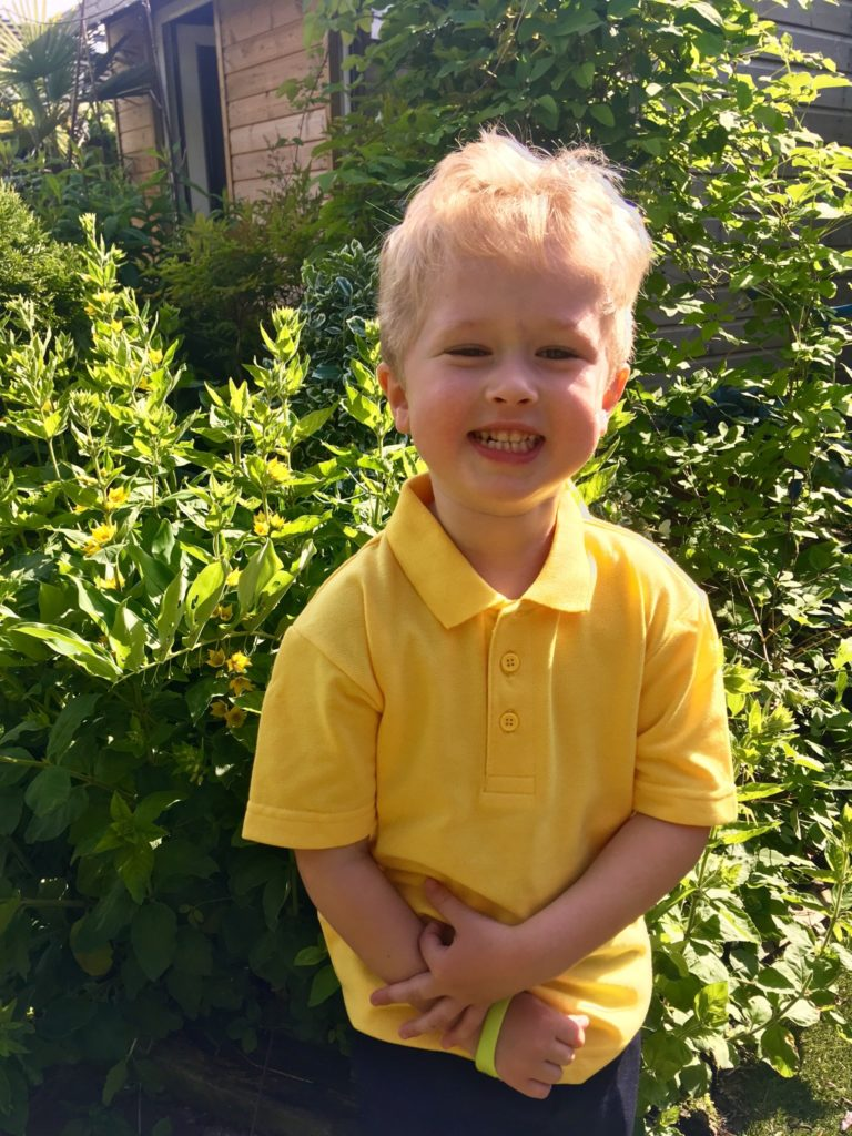 Lucas is stood outside next to a yellow flower plant wearing yellow polo shirt smiling at camera