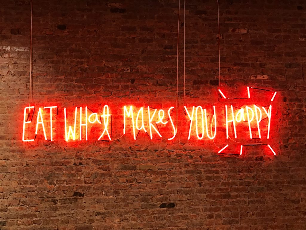 A neon sign saying eat what makes you happy against a brick wall