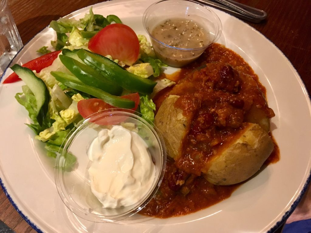 Jacket potato with chilli over it. On the side is salad and sour cream in a dish