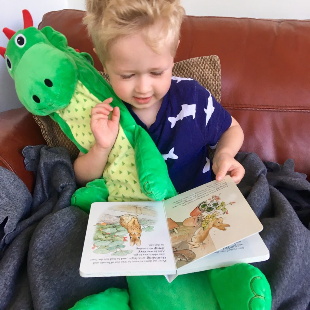 Lucas sat down reading a book holding onto dinosaur long hot water bottle teddy