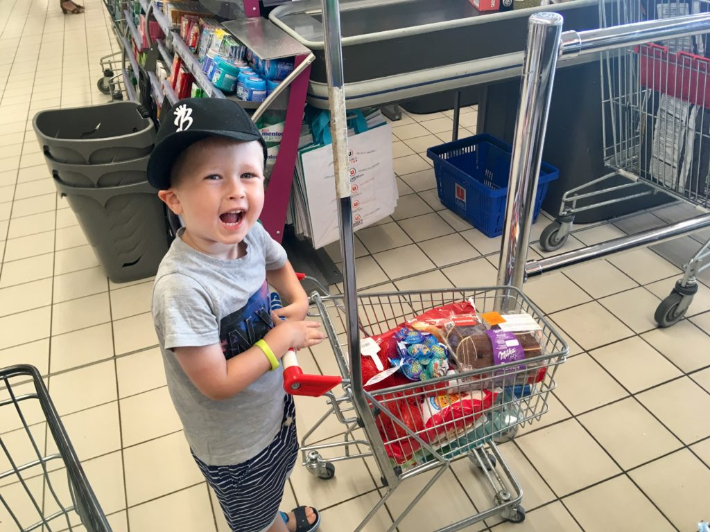 Lucas pushing a children's trolley at supermarket