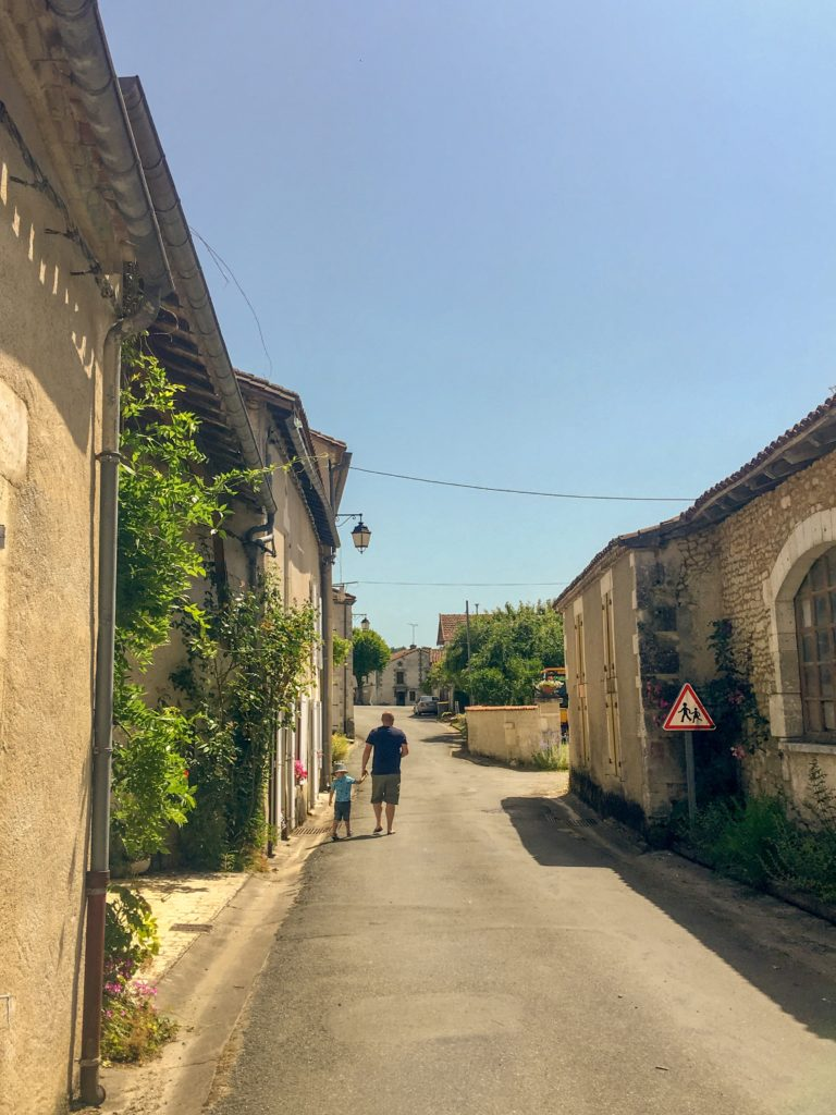 Lucas and D walking along a French village road