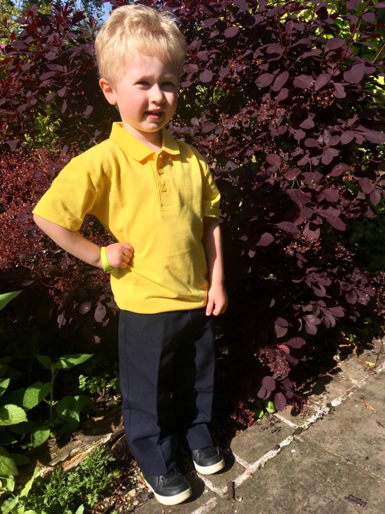 Lucas is stood outside wearing a yellow polo shirt and navy trousers