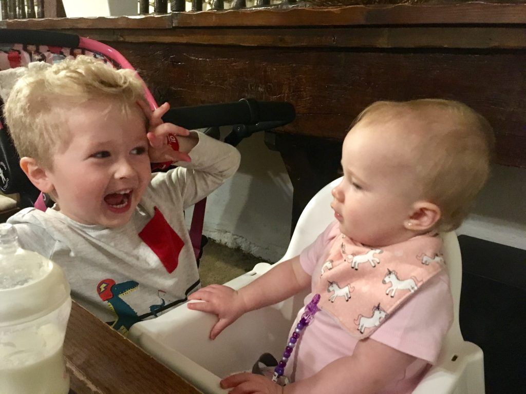 Baby girl in high chair with Lucas stood next to her smiling at her waving his hands