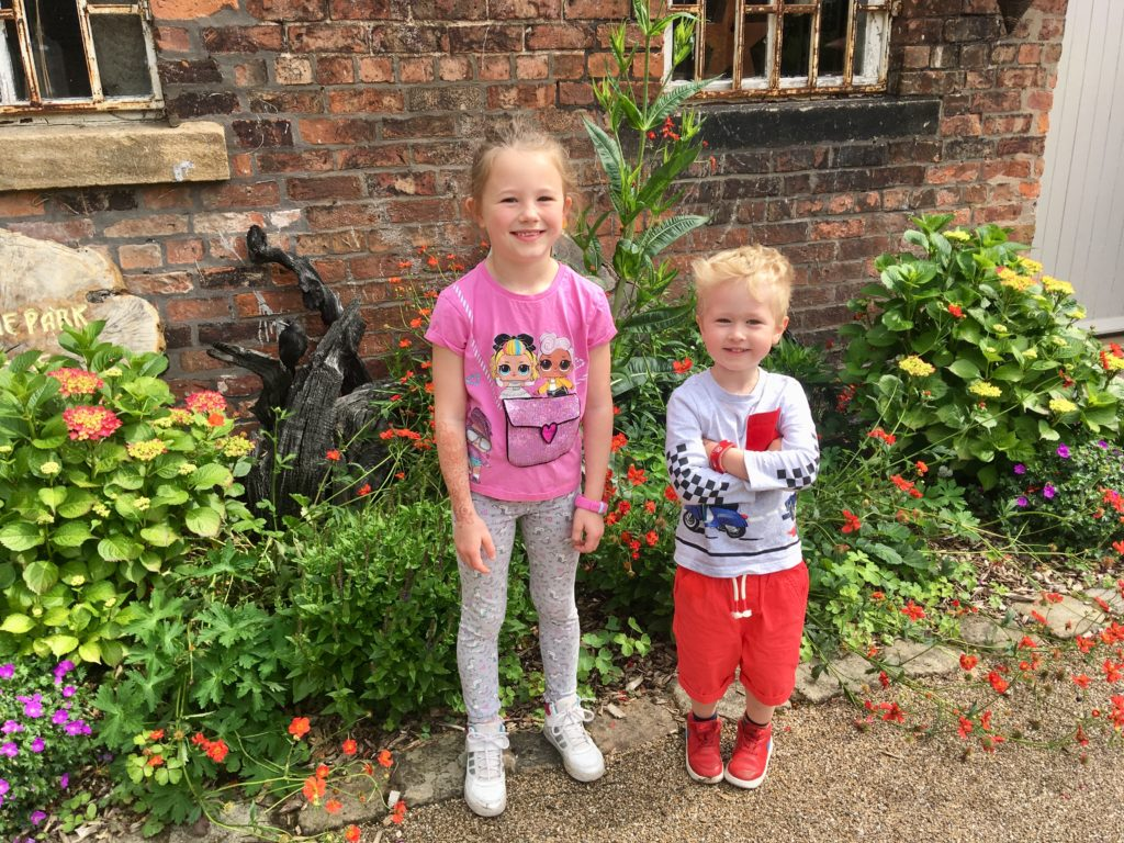 Lucas and his friends, a girl standing next to him in front of colourful flowers outside