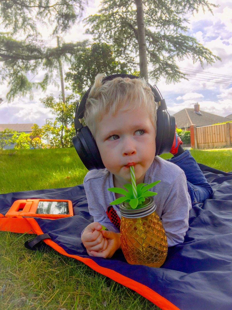 Lucas led outside on a blue blanket with his tablet next to him, wearing the black headphones and drinking from a pineapple cup