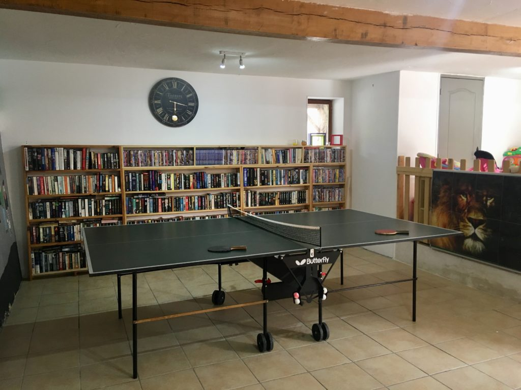 The games room. There is the table tennis table and behind a wall filled with books and dvds