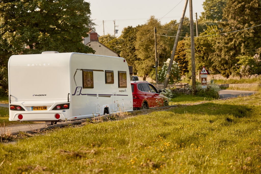 a red car pulling a 4 berth caravan along through country roads