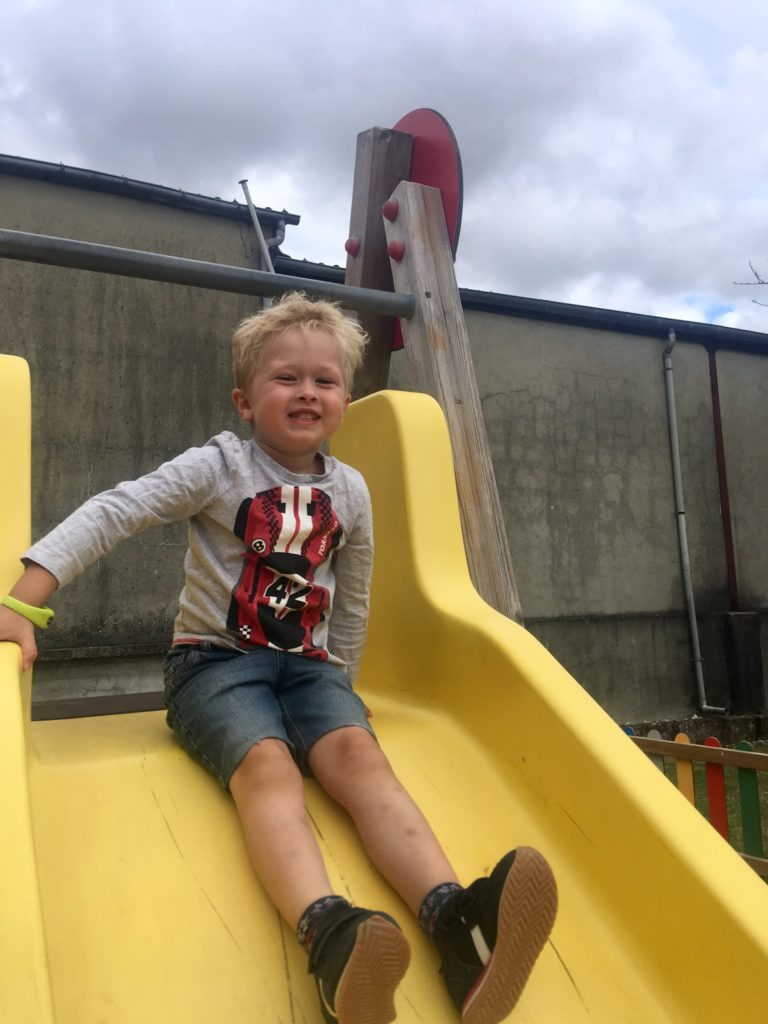 Active through play, Lucas is sat on the top of a yellow slide smiling at the camera