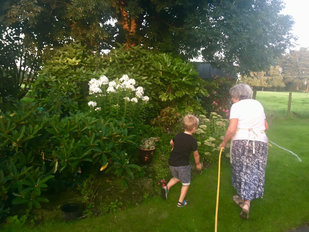 Lucas and grandma watering the garden