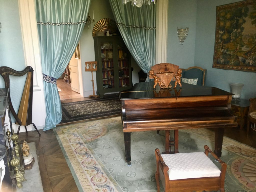 A piano room with draped curtains behind leading into another room