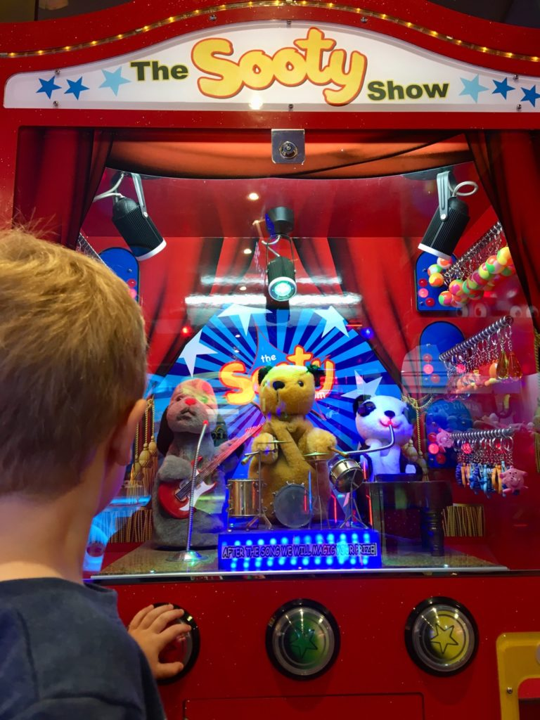 Lucas next to a sooty and sweep arcade machine