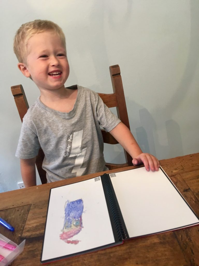 Lucas smiling showing his drawing on the rocketbook Everlast
