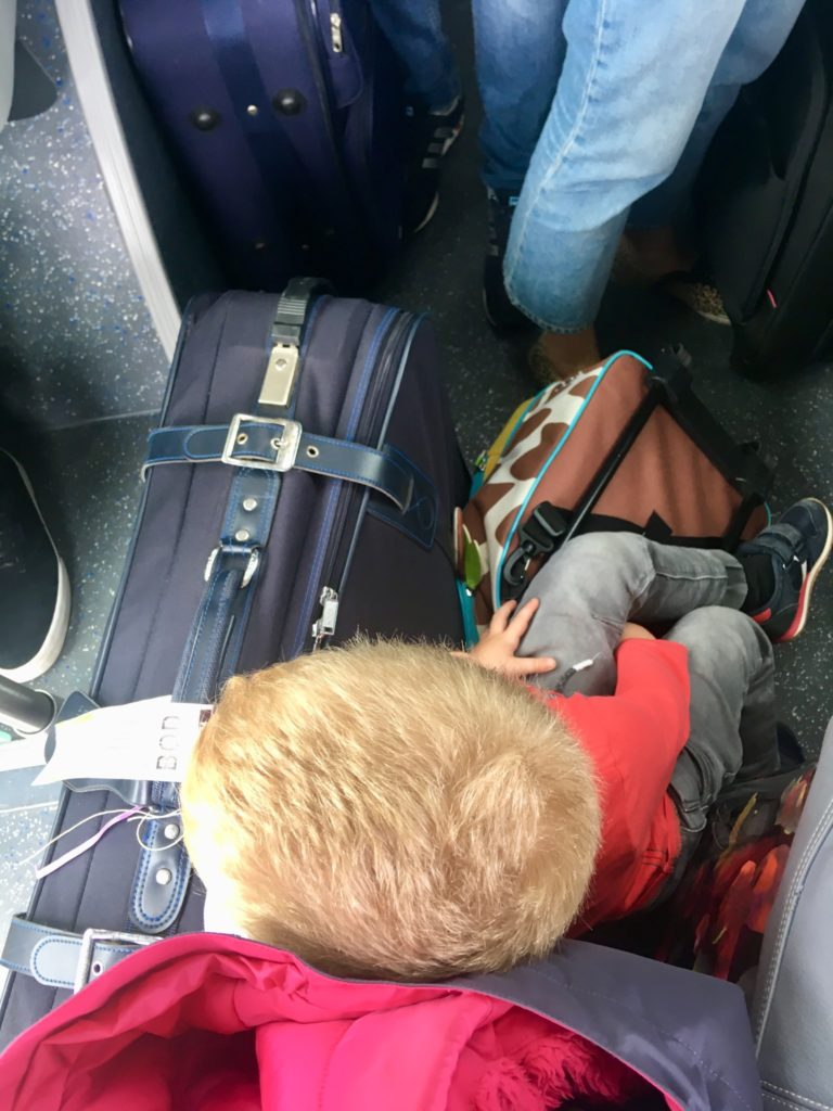 Lucas sat on the floor of the bus on suitcases