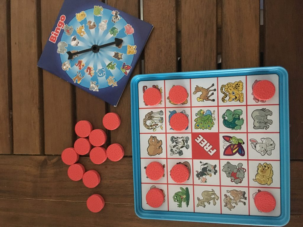 Take n play bingo on the table showing the board, red counters and spinner