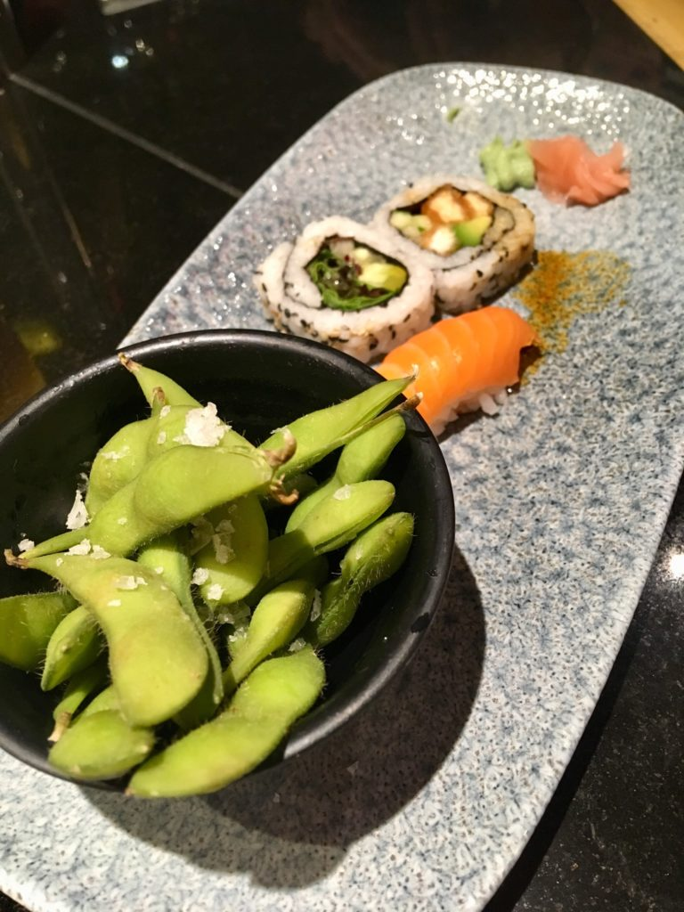 Edamame in a black bowl on a grey plate