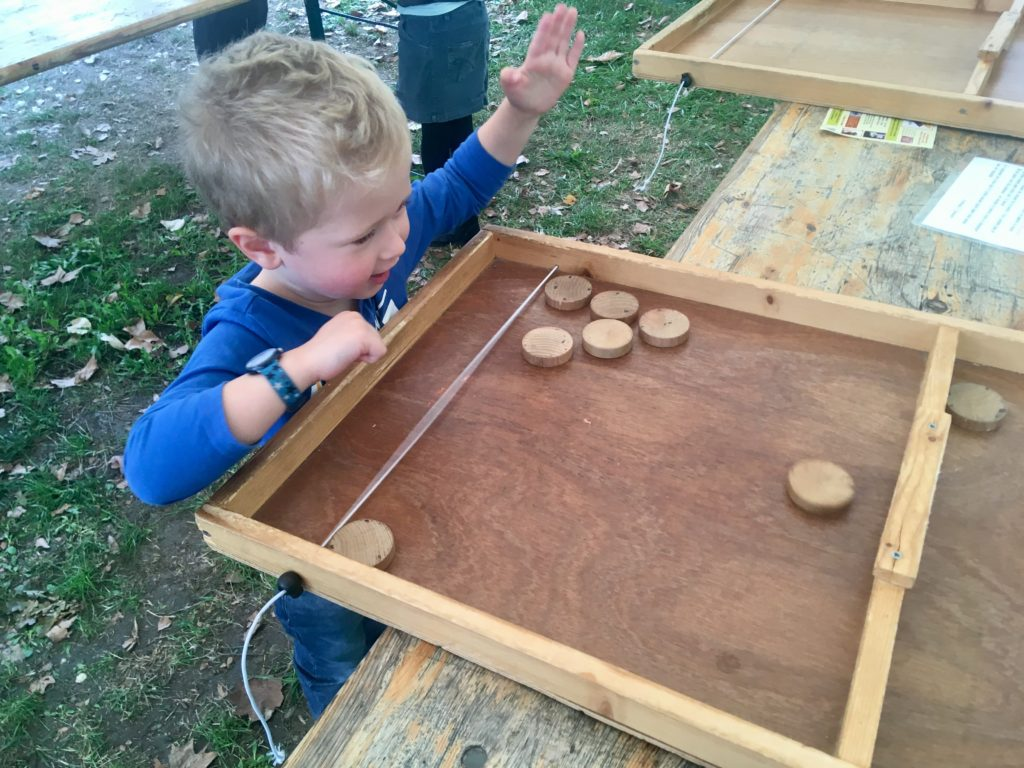 Lucas playing an outdoor wooden game