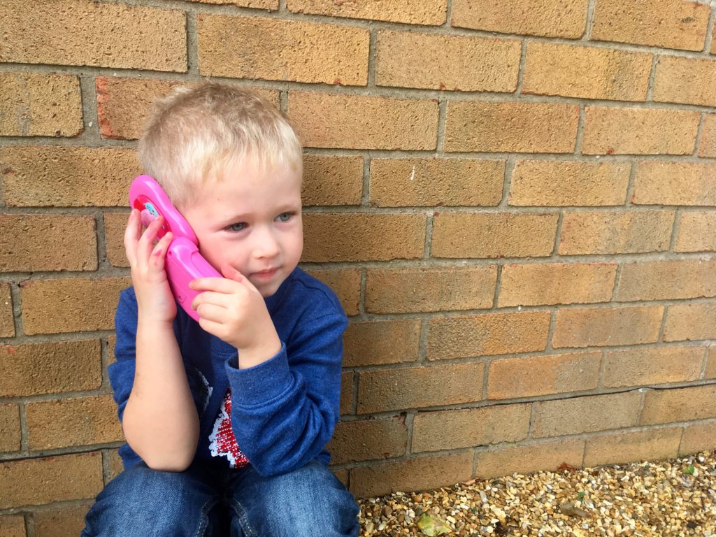 Lucas crouching down holding the Peppa phone to his ear