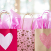three gift bags with hearts on in a variety of pinks and golds