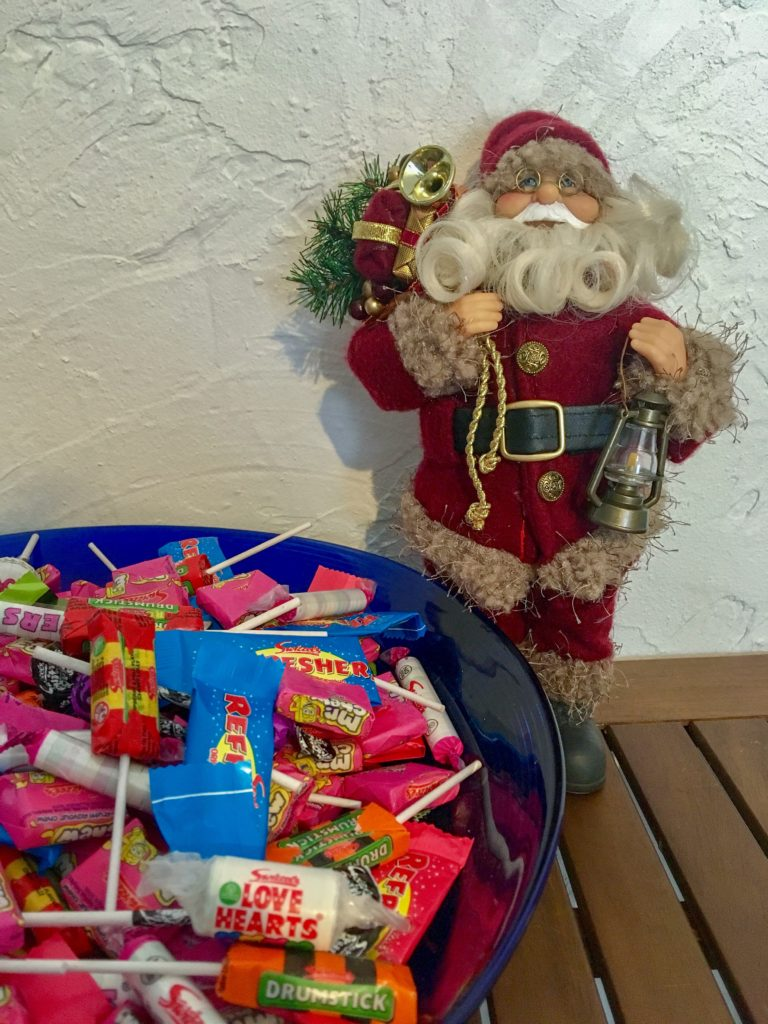 A bowl full of swizzles sweets next to a Father Christmas decoration