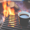 a cup of coffee and an outdoor fire in the background
