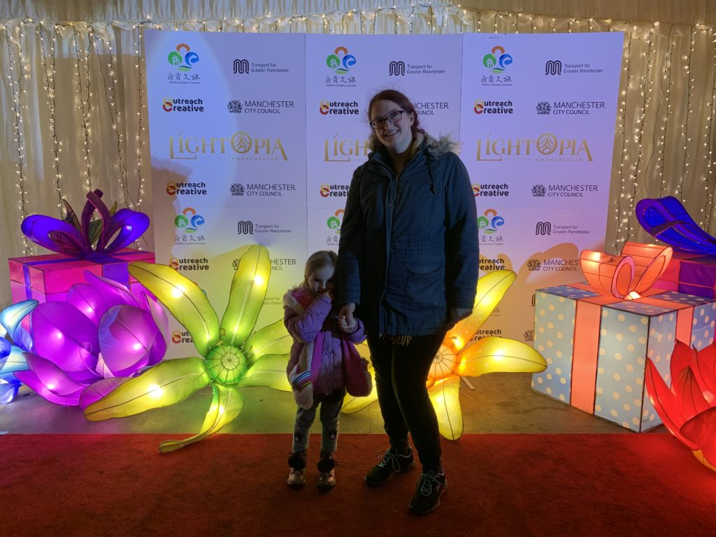 Raimy and spike stood in front of a lightopia poster with lit up flowers around them at Lightopia Manchester