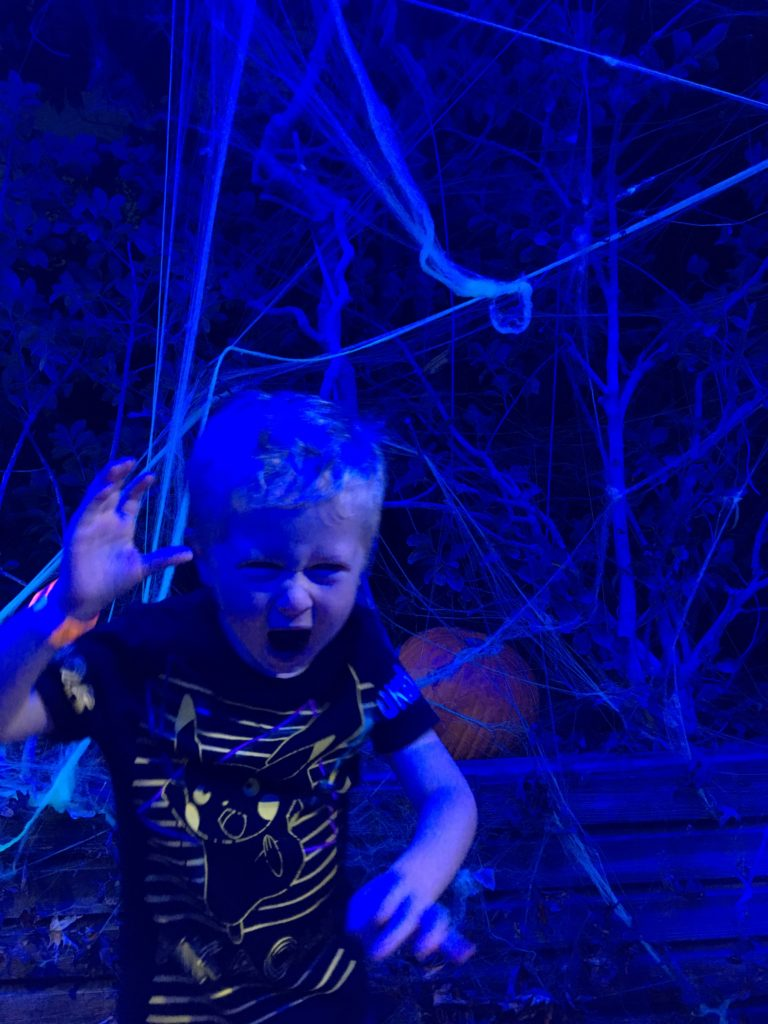 Futuroscope France review. Lucas doing a scary face with blue lighting and cobwebs behind him