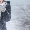 a lady in a black coat and gret fingerless gloves blowing snow from her hands