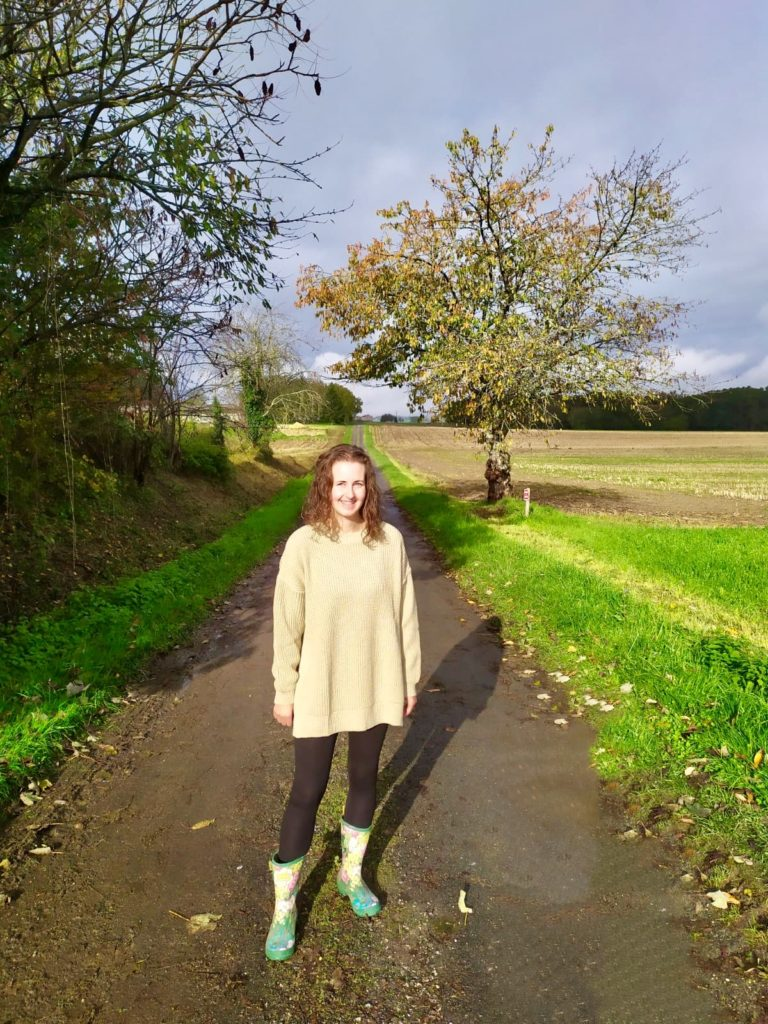 I'm standing on a country lane wearing a Femme Luxe stone jumper, black leggings and floral wellies