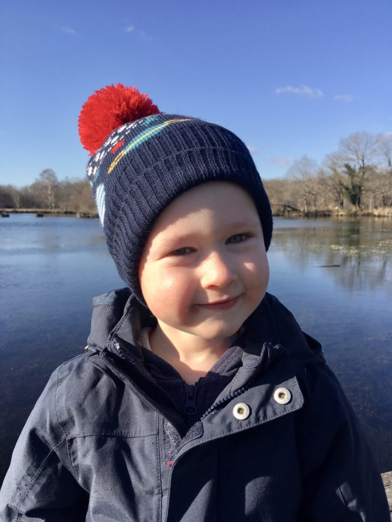 Lucas looking at the camera smiling wearing a navy and red bobble hat and navy coat
