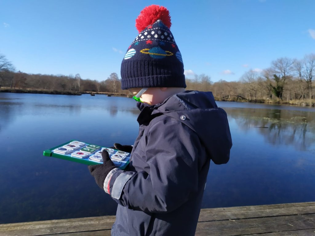Lucas is side on to the camera. You can see a lake behind him. He is looking down at his magnet board