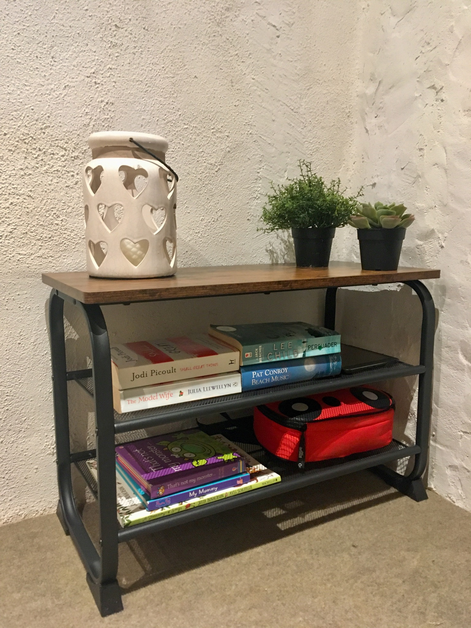 The vasagle shoe bench with a cut out heart candle holder and plants on the top, books on both mesh shelves