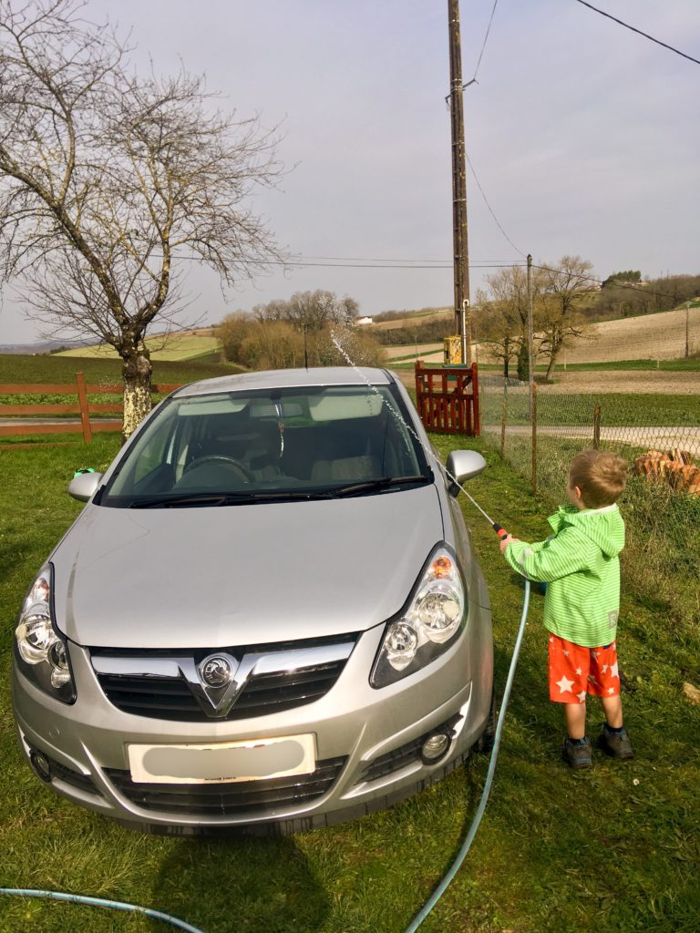 Lucas washing the car with a hose pipe. It's a silver corsa and lucas is wearing a green stripy jacket and starry shorts