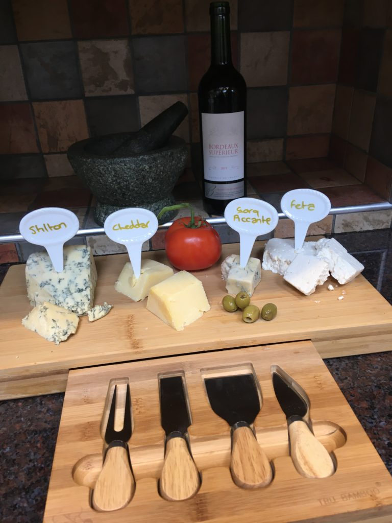 Bamboo cheese board showing tools in front. The board has a selection of cheeses in, a tomato and olives