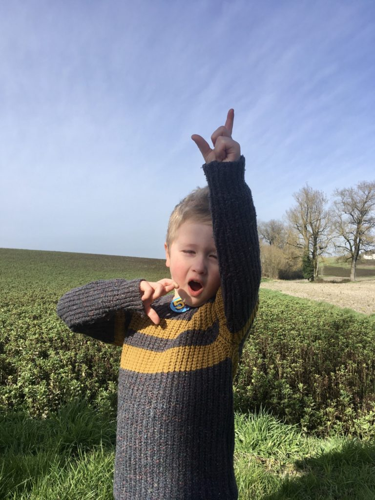 Lucas outside with one hand up, mouth open and eyes closed. Wearing a jumper and 5 badge