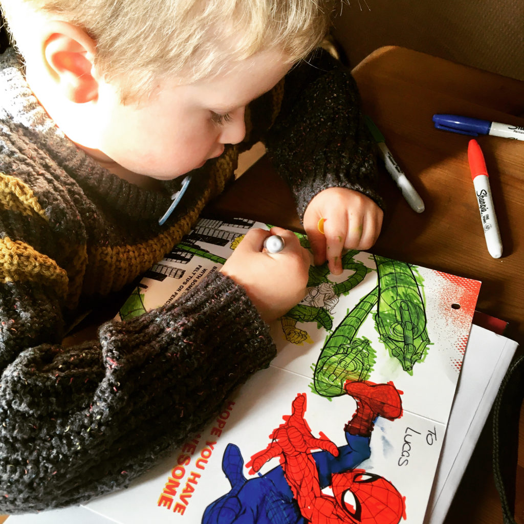 Lucas colouring the inside of his Spider-Man birthday card