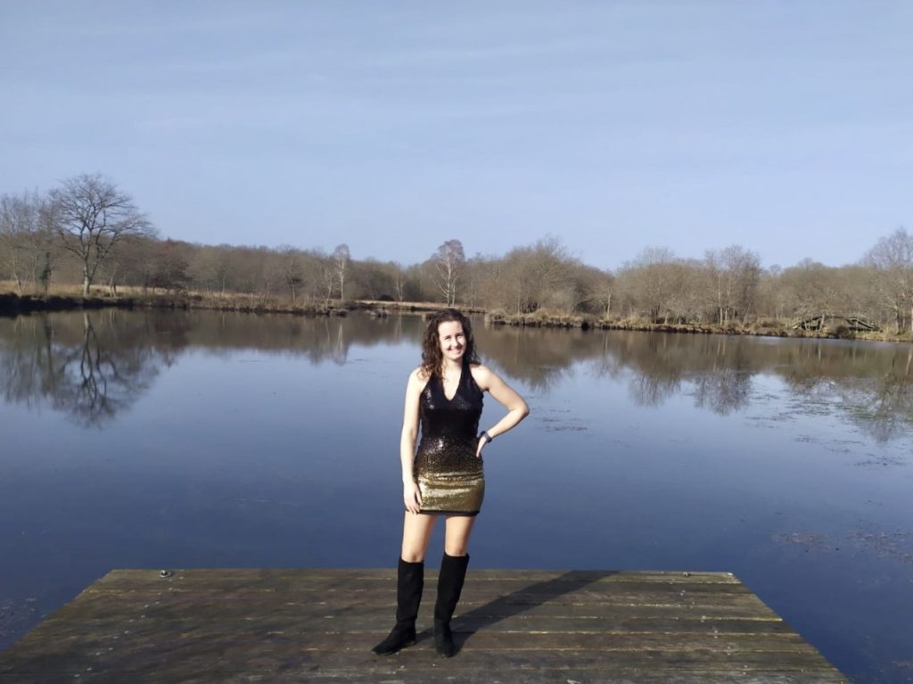 i am wearing the femme luxe sequin halterneck dress, you can see a lake behind me