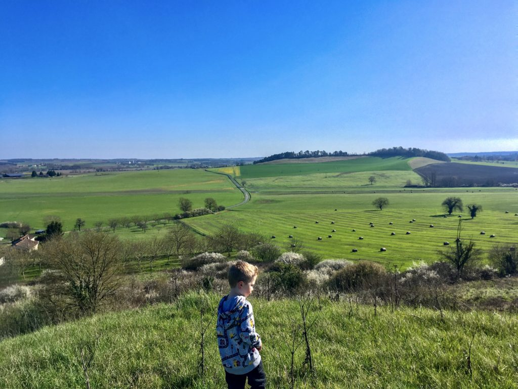 Lucas walking on a hill, you can see countryside for miles around