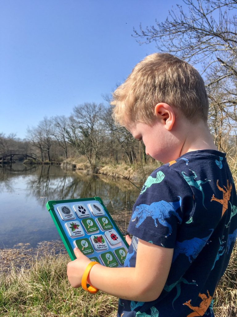 Lucas looking down at the seekers scavenger hunt board. You can see a lake in the background