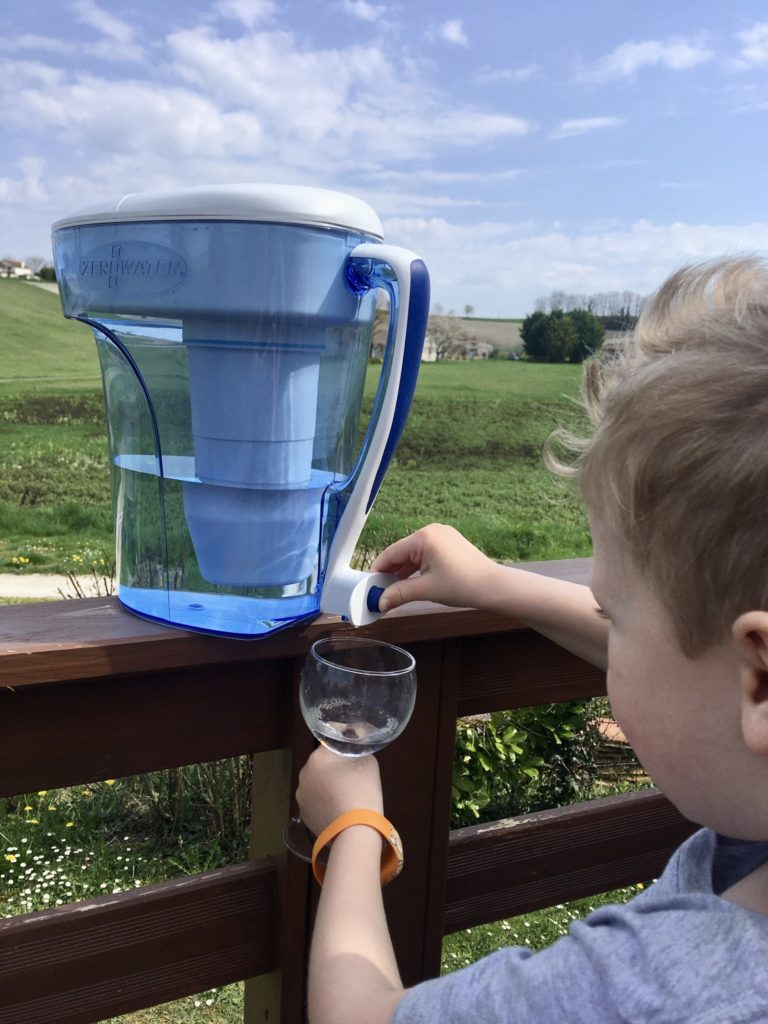 Lucas pouring water out of the jug from the button at the back