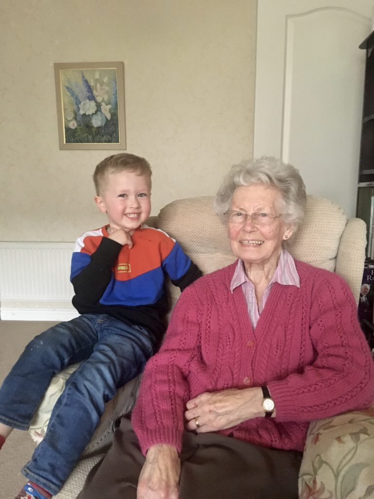 Lucas and his great grandma sat on the sofa looking at the camera