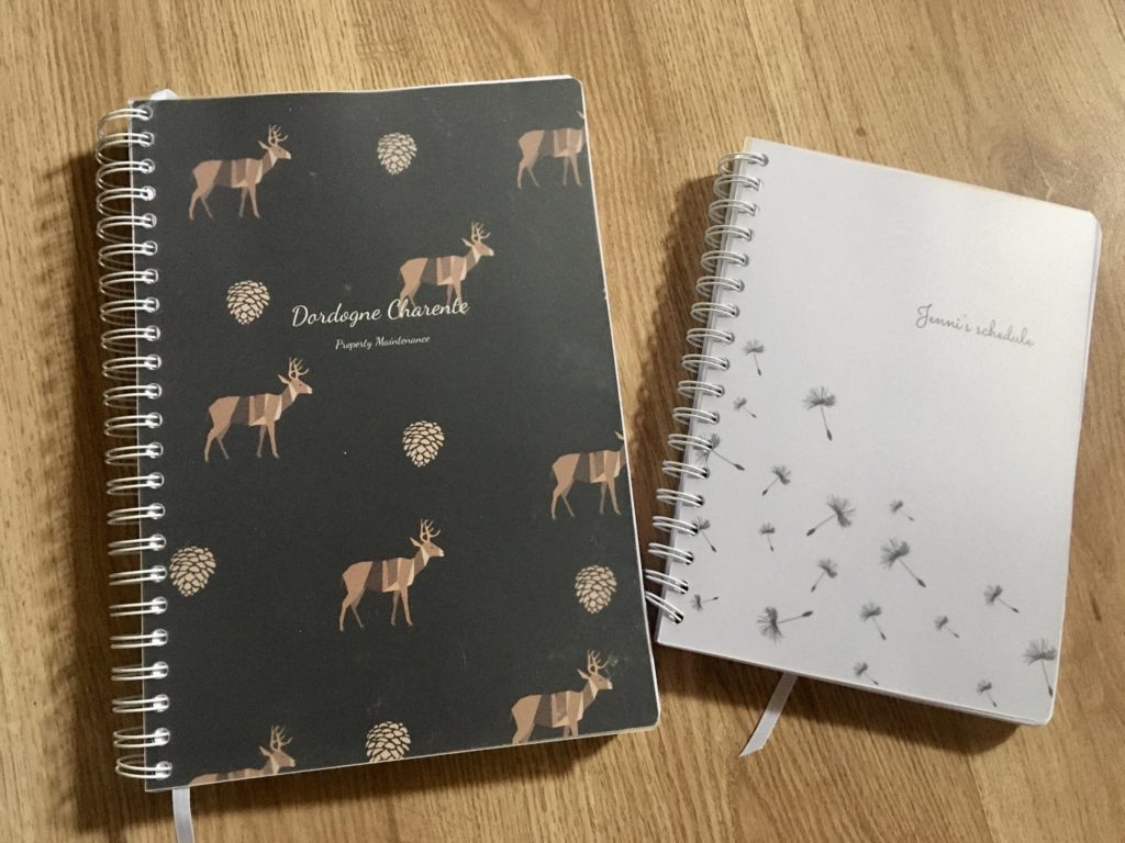 2 diaries from Toad Diaries. One is white with dandelions on and smaller than the A4 one next to it which is black with deer on